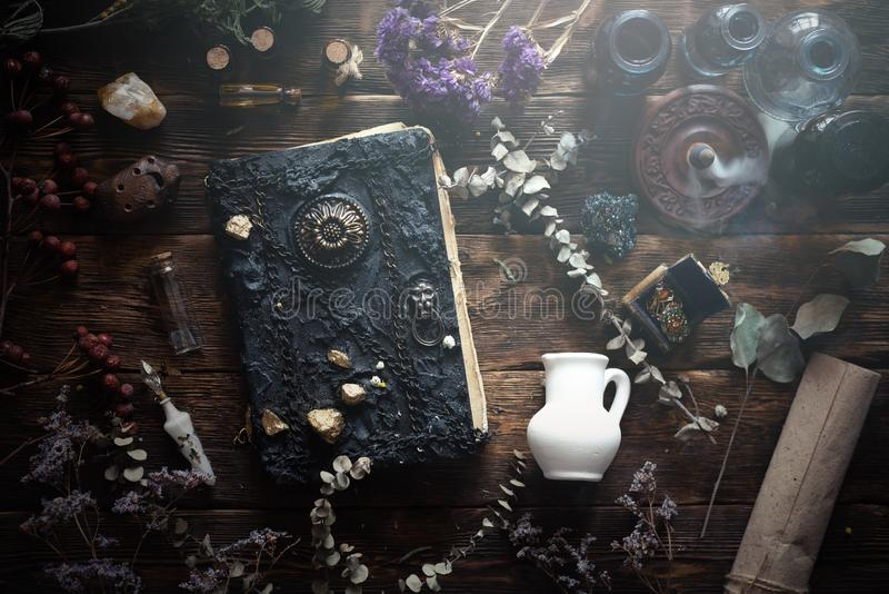 Magic book. Magic recipe book and a magic potions on a table. Witchcraft background with copy space. Druid or witch doctor table stock image