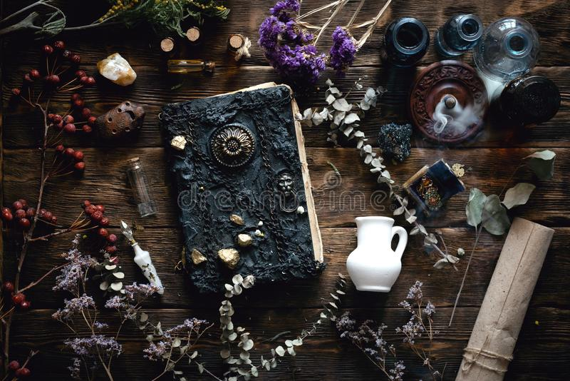 Magic book. Magic recipe book and a magic potions on a table. Witchcraft background with copy space. Druid or witch doctor table royalty free stock photos