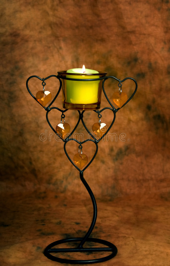 Magic ritual. Magic candle in candlestick over orange background royalty free stock image
