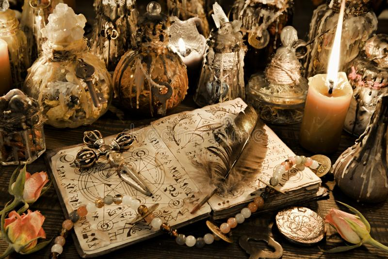 Magic ritual bottles with open witch book, quill and cross in candlelight on the table. Wicca, esoteric and Halloween background. No foreign text, all symbols stock image