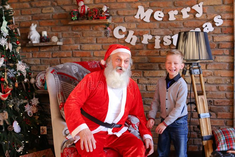 Magic Santa Claus and little boy fooling around and have fun tog. Christmas grandfather tickles and cute plays along with energetic child, sitting on large royalty free stock images