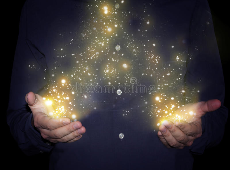 Magic sparkles in hands. Magic sparkles glowing in man hands royalty free stock images