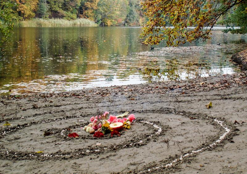 Magic spiral works next to a lake, wicca altar. Pagan religion. stock photos