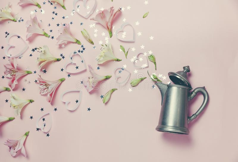 Magic spring appearance of flovers and hearts from vintage kettle on pink background. top view, flat lay. romantic spring picture stock photography