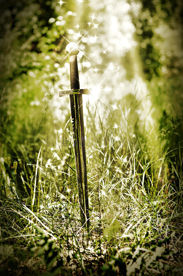 Magic sword. Stuck in the ground stock photography