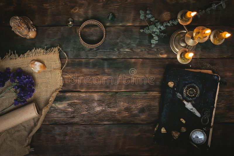Magic table. Ancient magic book and a pocket watch in the light of burning candle on a wooden table background with copy space. Spell book stock photo