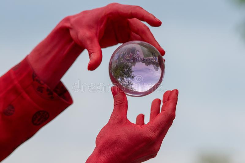 Magic trick balancing glass cystal ball in the air between hands. Man with red hands dressed as the devil holds and plays with an glass crystal ball containing royalty free stock photography