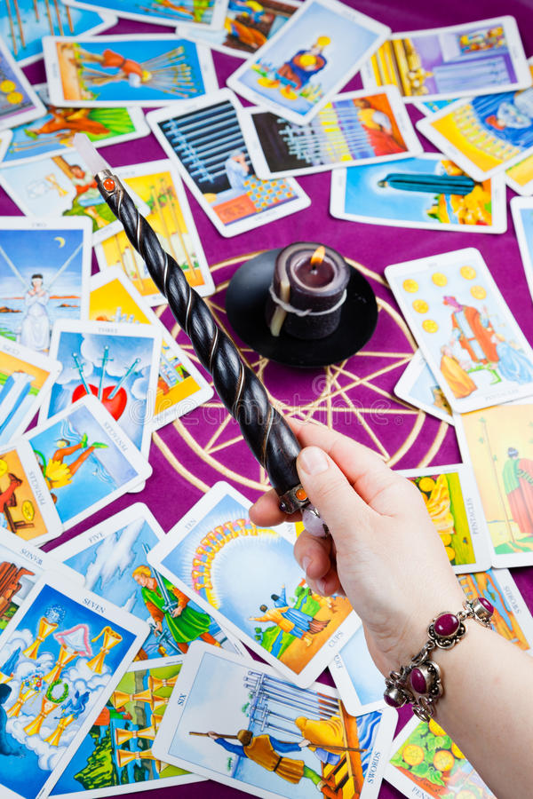 Magic wand held in hand. Background: tarot cards and magic candle stock image