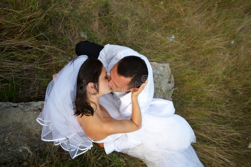 The magic of the wedding kiss between lovers. Beautiful couple being passionate about each other in their wedding day