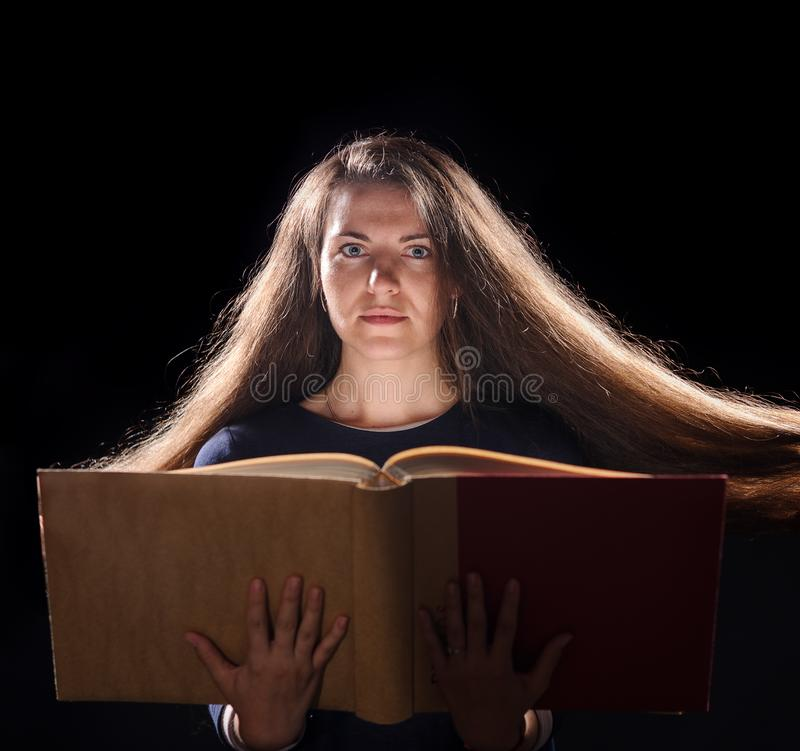 Magic Woman reading a book. black background. Beautiful, beauty, brunette, dark, evil, face, fairy, fantasy, female, girl, golden, gothic, hair, halloween royalty free stock image