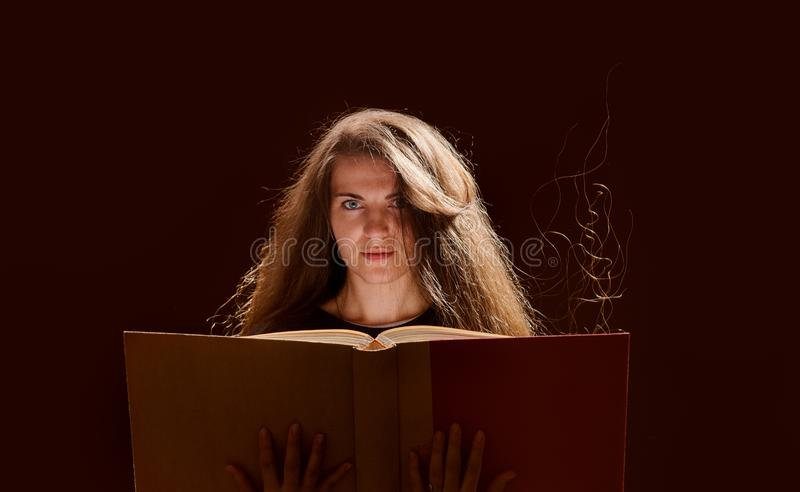 Magic Woman reading a book. black background. Beautiful, beauty, brunette, dark, evil, face, fairy, fantasy, female, girl, golden, gothic, hair, halloween stock photos