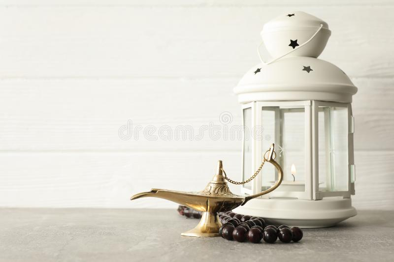 Magical Aladdin Lamp with prayer beads and Ramadan lantern on grey table royalty free stock images