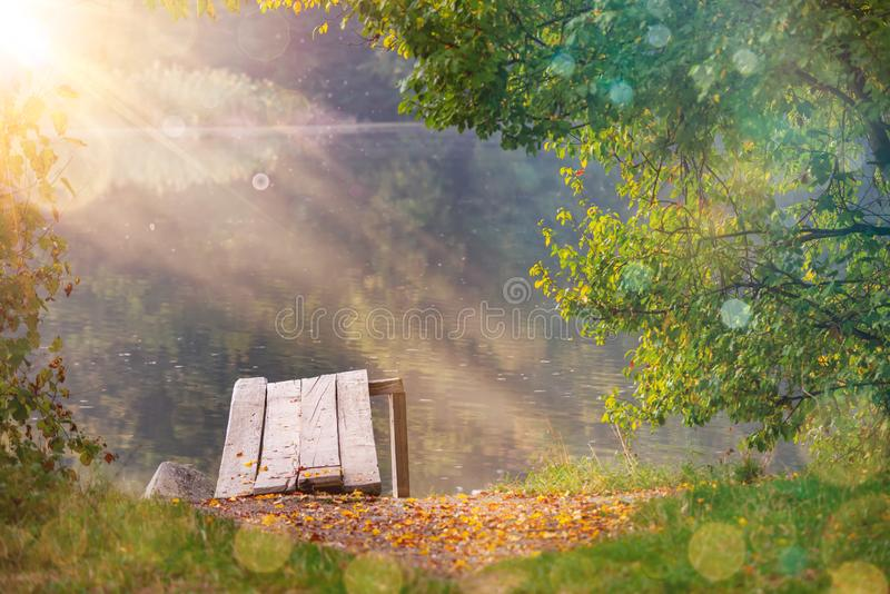 Magical autumn sun rays over a lake and a boat dock, perfect spot for meditation. Natural frame fall landscape with tree royalty free stock images