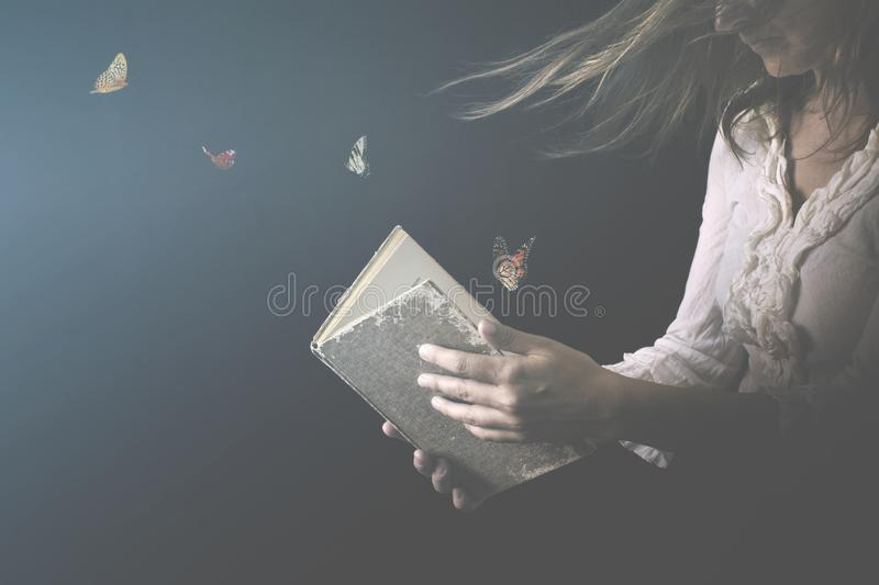 Magical butterflies come out of a book read by a woman. Surreal moment about magical butterflies come out of a book read by a woman stock photography