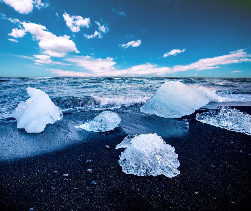 Magical charming beautiful landscape with a piece of ice like a sculpture on the Diamond beach near glacier lagoon Jokulsarlon, stock photography