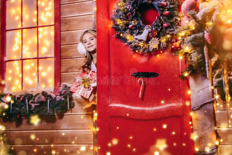 Magical christmas house. Beautiful child girl peeking out of the door of her house decorated for Christmas and holding a gift. Time for miracles stock photos
