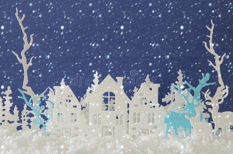 Magical Christmas paper cut winter background landscape with houses, trees, deer and snow in front of blue background. Magical Christmas paper cut winter royalty free stock image