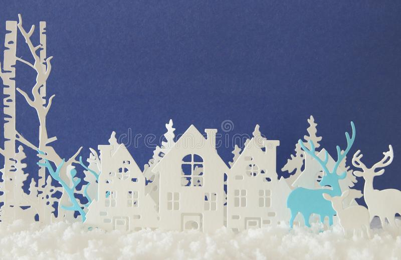 Magical Christmas paper cut winter background landscape with houses, trees, deer and snow in front of blue background. Magical Christmas paper cut winter stock photography