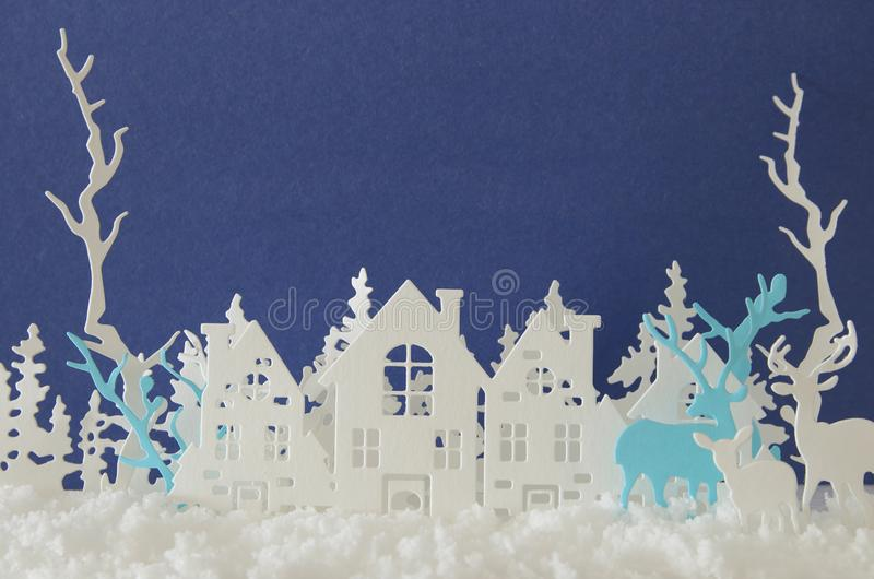 Magical Christmas paper cut winter background landscape with houses, trees, deer and snow in front of blue background. royalty free illustration
