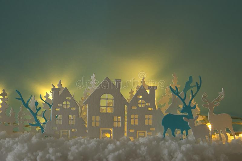 Magical Christmas paper cut winter background landscape with houses, trees, deer and snow in front of gold lights background. Magical Christmas paper cut winter stock photos