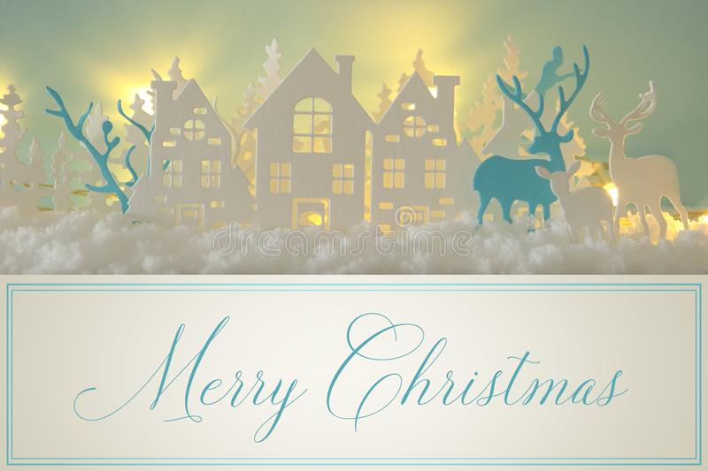 Magical Christmas paper cut winter background landscape with houses, trees, deer and snow in front of gold lights background. Magical Christmas paper cut winter stock images
