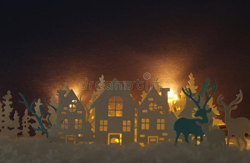 Magical Christmas paper cut winter background landscape with houses, trees, deer and snow in front of gold lights background. Magical Christmas paper cut winter royalty free stock photos