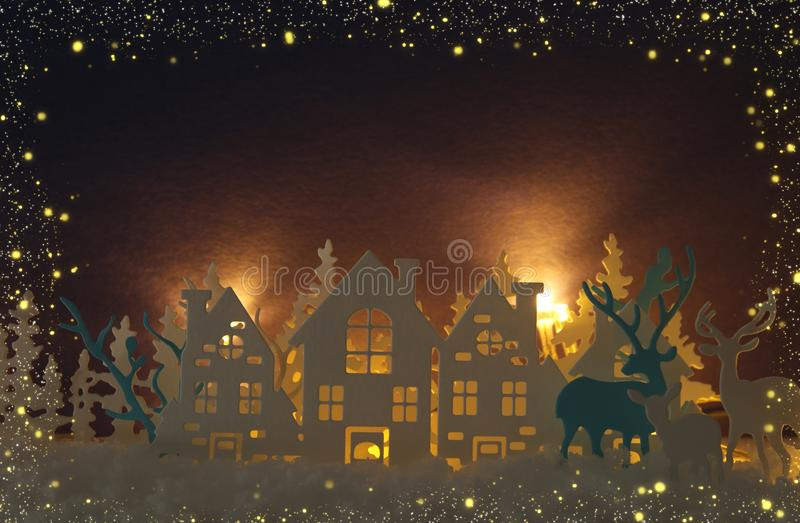 Magical Christmas paper cut winter background landscape with houses, trees, deer and snow in front of gold lights background. Magical Christmas paper cut winter royalty free stock image