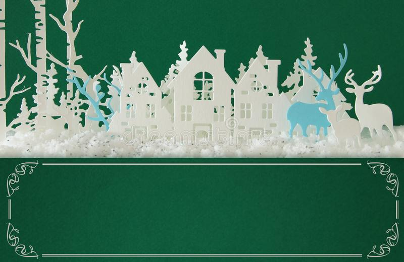 Magical Christmas paper cut winter background landscape with houses, trees, deer and snow in front of green background. Magical Christmas paper cut winter royalty free stock images