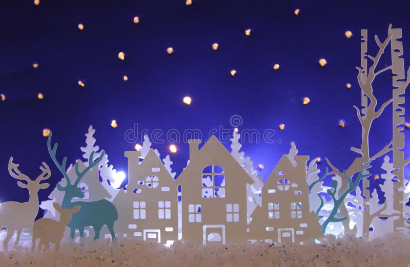 Magical Christmas paper cut winter background landscape with houses, trees, deer and snow in front of night starry sky background. vector illustration