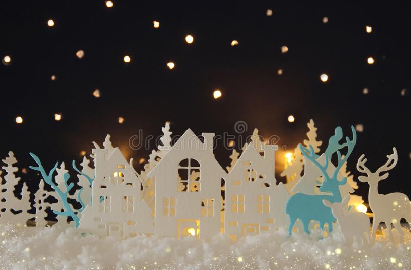 Magical Christmas paper cut winter background landscape with houses, trees, deer and snow in front of night starry sky background. Magical Christmas paper cut royalty free stock photos