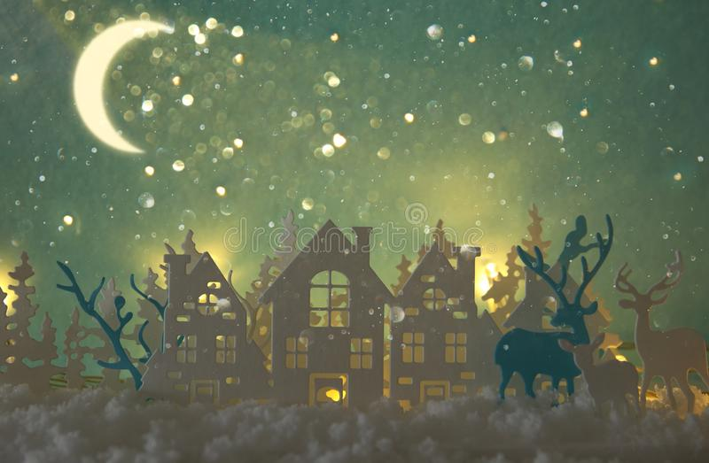 Magical Christmas paper cut winter background landscape with houses, trees, deer and snow in front of night starry sky background. Magical Christmas paper cut stock photo