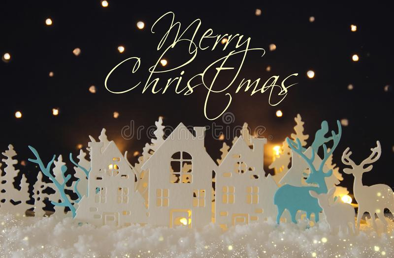 Magical Christmas paper cut winter background landscape with houses, trees, deer and snow in front of night starry sky background. stock images