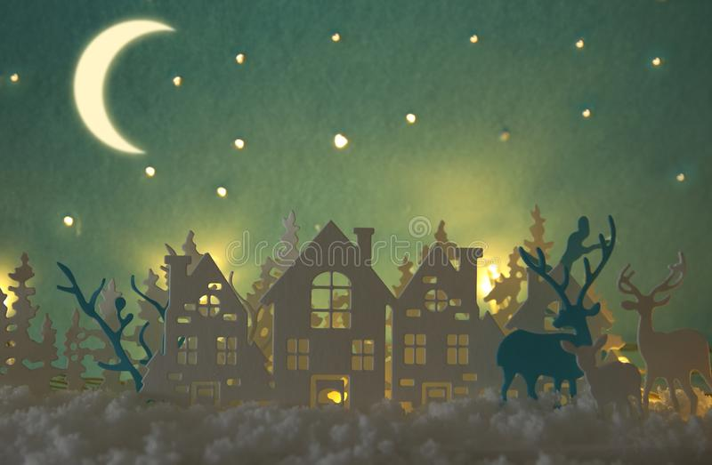 Magical Christmas paper cut winter background landscape with houses, trees, deer and snow in front of night starry sky background. Magical Christmas paper cut stock images