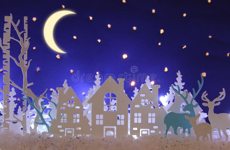Magical Christmas paper cut winter background landscape with houses, trees, deer and snow in front of night starry sky background. Magical Christmas paper cut royalty free stock photo