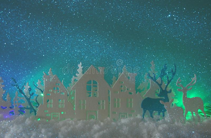 Magical Christmas paper cut winter background landscape with houses, trees, deer and snow in front of northern lights background. vector illustration