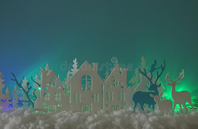 Magical Christmas paper cut winter background landscape with houses, trees, deer and snow in front of northern lights background. Magical Christmas paper cut stock photos