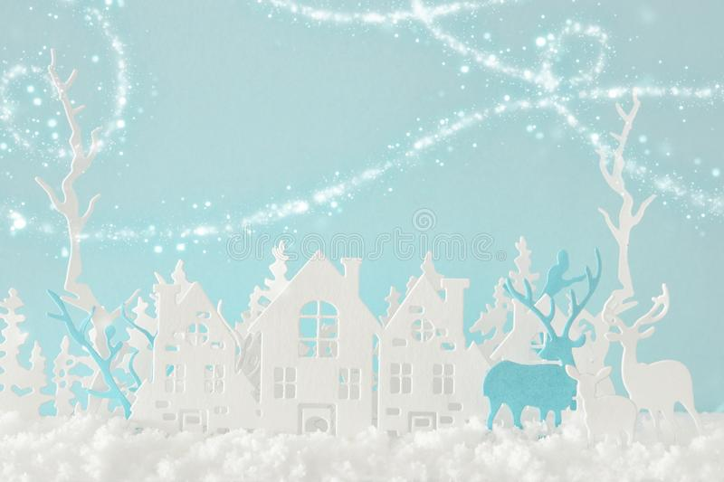 Magical Christmas paper cut winter background landscape with houses, trees, deer and snow in front of pastel blue background. Magical Christmas paper cut winter stock photo
