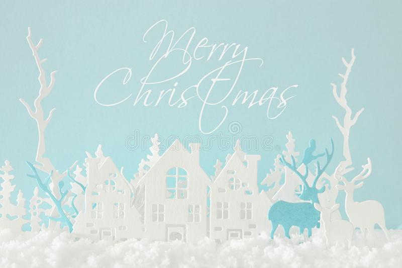 Magical Christmas paper cut winter background landscape with houses, trees, deer and snow in front of pastel blue background. royalty free illustration