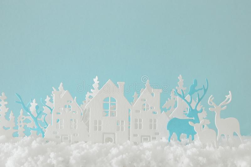 Magical Christmas paper cut winter background landscape with houses, trees, deer and snow in front of pastel blue background. Magical Christmas paper cut winter royalty free stock image