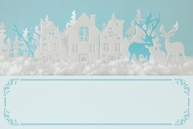 Magical Christmas paper cut winter background landscape with houses, trees, deer and snow in front of pastel blue background. Magical Christmas paper cut winter royalty free stock photos