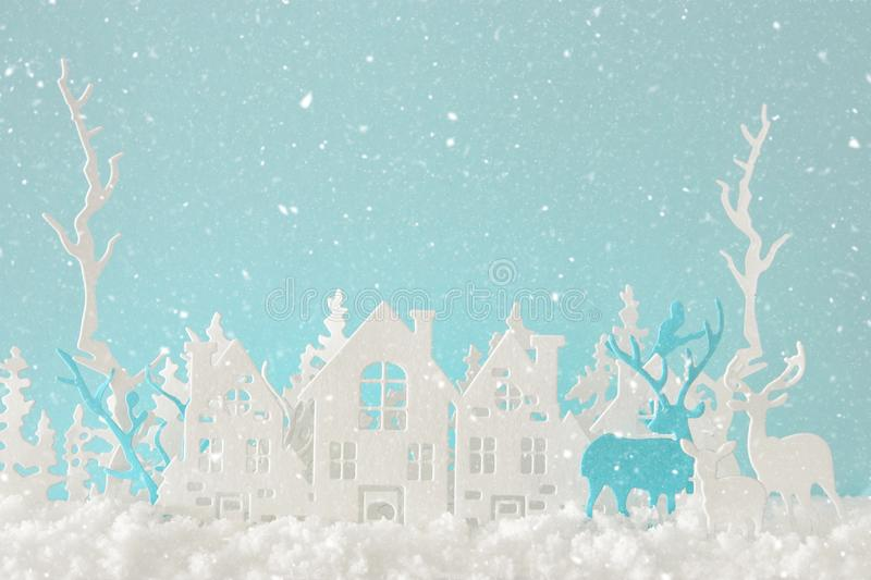 Magical Christmas paper cut winter background landscape with houses, trees, deer and snow in front of pastel blue background. Magical Christmas paper cut winter royalty free stock photography