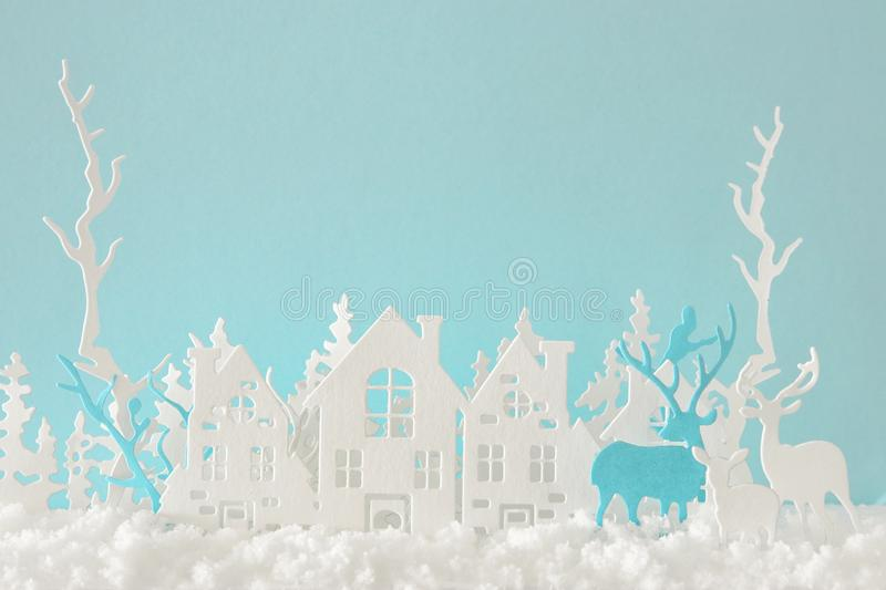 Magical Christmas paper cut winter background landscape with houses, trees, deer and snow in front of pastel blue background. Magical Christmas paper cut winter royalty free stock images