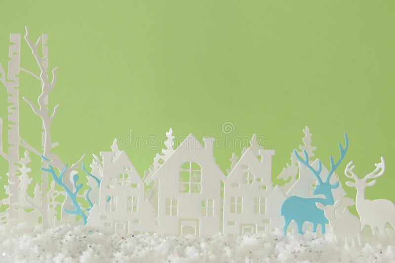 Magical Christmas paper cut winter background landscape with houses, trees, deer and snow in front of pastel green background. Magical Christmas paper cut royalty free stock images