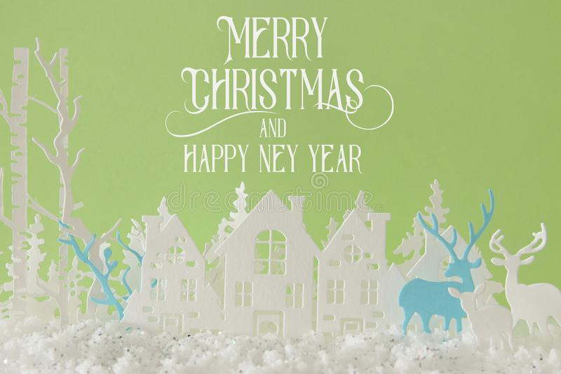 Magical Christmas paper cut winter background landscape with houses, trees, deer and snow in front of pastel green background. Magical Christmas paper cut royalty free stock photo