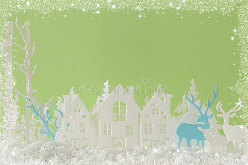 Magical Christmas paper cut winter background landscape with houses, trees, deer and snow in front of pastel green background. Magical Christmas paper cut royalty free stock photography