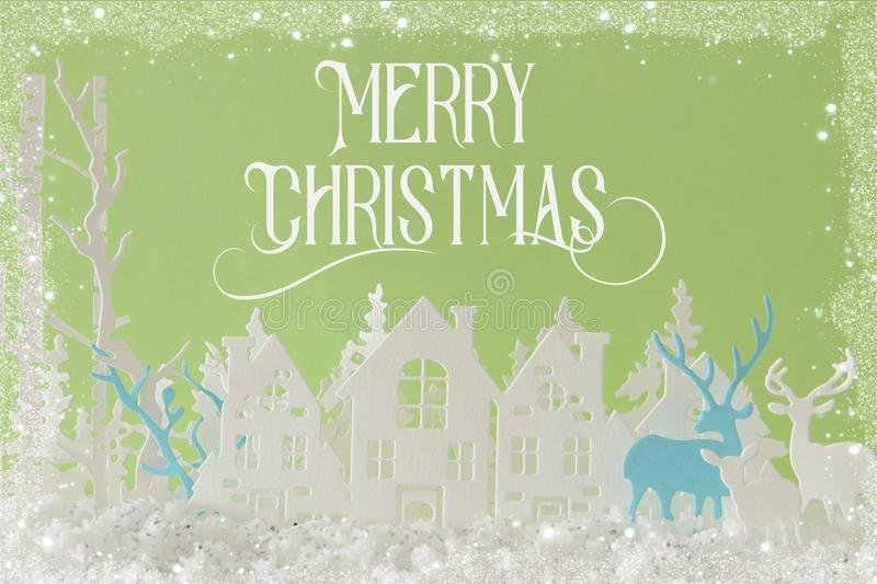 Magical Christmas paper cut winter background landscape with houses, trees, deer and snow in front of pastel green background. Magical Christmas paper cut stock photography