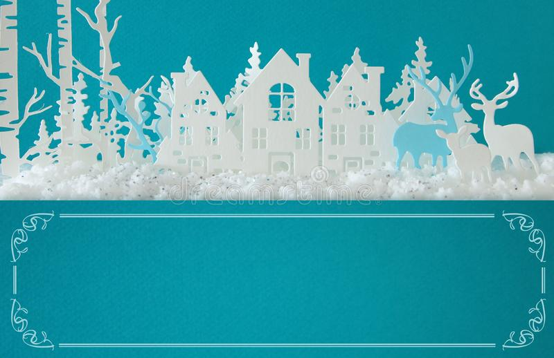 Magical Christmas paper cut winter background landscape with houses, trees, deer and snow in front of turquoise background. Magical Christmas paper cut winter stock photos