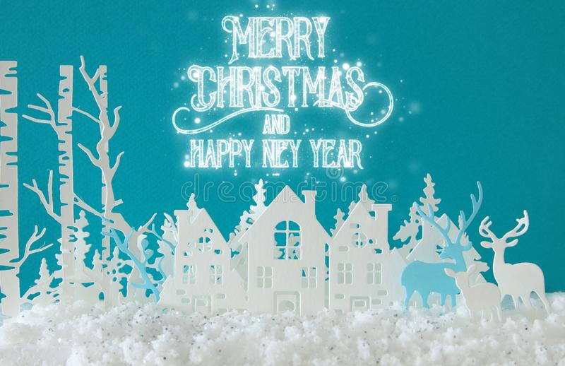 Magical Christmas paper cut winter background landscape with houses, trees, deer and snow in front of turquoise background. Magical Christmas paper cut winter stock photo