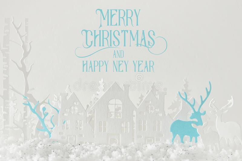 Magical Christmas paper cut winter background landscape with houses, trees, deer and snow in front of white background. Magical Christmas paper cut winter stock photo