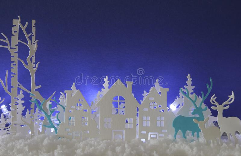 Magical Christmas paper cut winter background landscape with houses, trees, deer and snow in front of white lights background. stock illustration